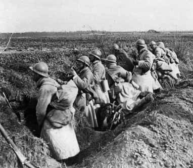 A squad occupies their freshly dug fox-holes along a roadside, Somme, 1918.