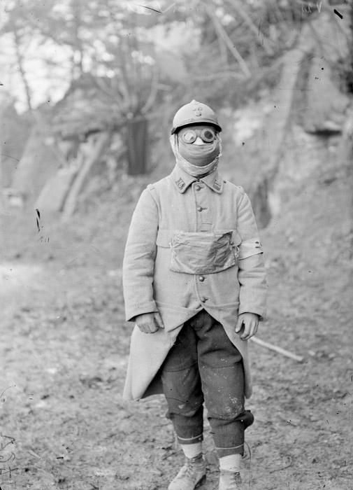 An anonymous soldier dons a P2 gas mask and goggles. (1915)