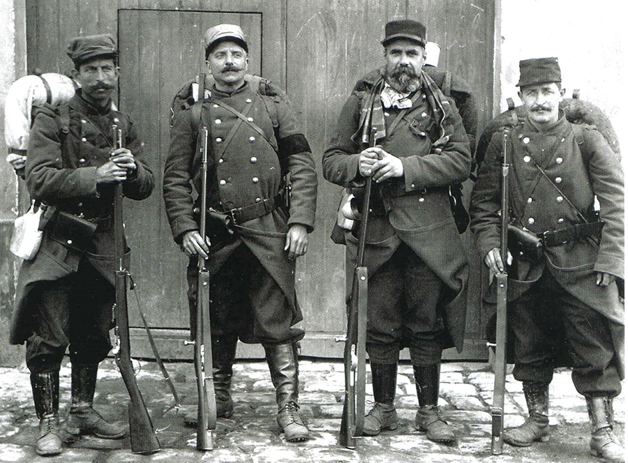 A group of old territorials, poorly equipped and armed with obsolete Gras rifles but stalwart nonetheless. One wears a mourning arm band. (1914)