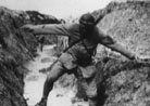 A runner attempts to pass a flooded trench.