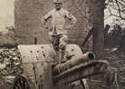 A telephonist stands perches on top of a German 77 mm gun in 1918.