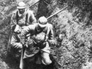 Two men carry out a wounded comrade.